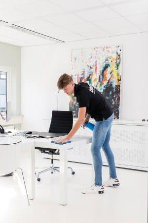 Een schoonmaker van schoonmaakbedrijf Blinck aan het werk in een kantoor.