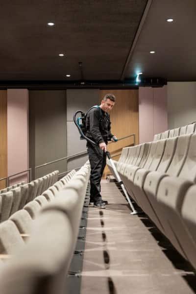 Vaste schoonmaker voor media en entertainment maakt theaterzaal schoon.