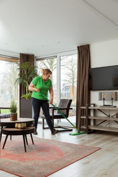 Vaste medewerker van Blinck voor recreatie en leisure maakt vakantiehuisje schoon.