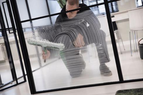 Glazenwasser maakt ramen in het kantoor schoon.